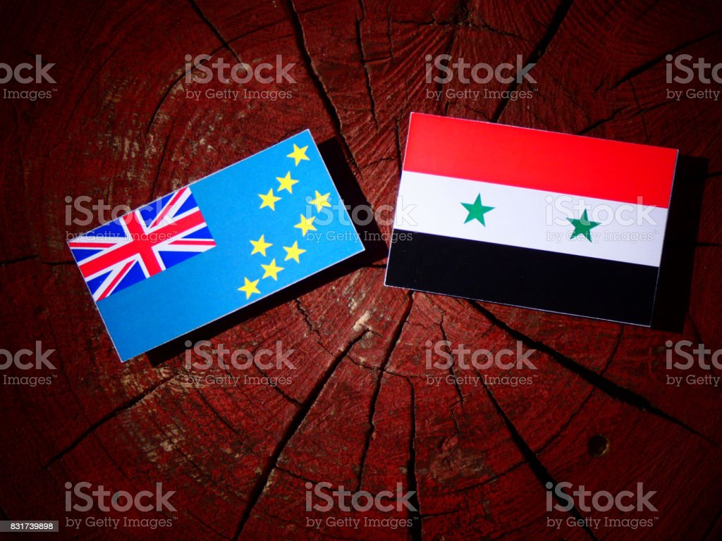 Tuvalu flag with Syrian flag on a tree stump isolated stock photo