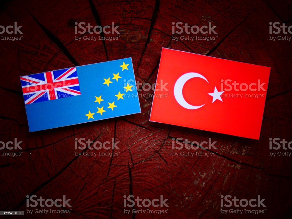 Tuvalu flag with Turkish flag on a tree stump isolated stock photo