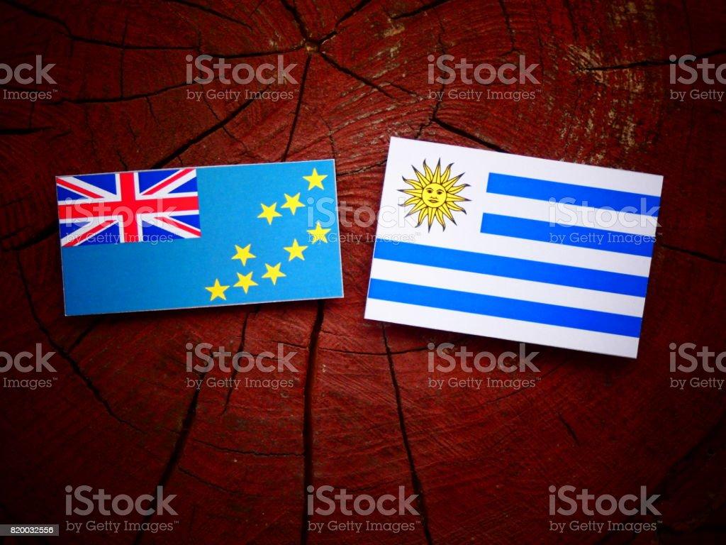 Tuvalu flag with Uruguaian flag on a tree stump isolated stock photo