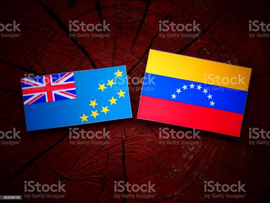 Tuvalu flag with Venezuelan flag on a tree stump isolated stock photo