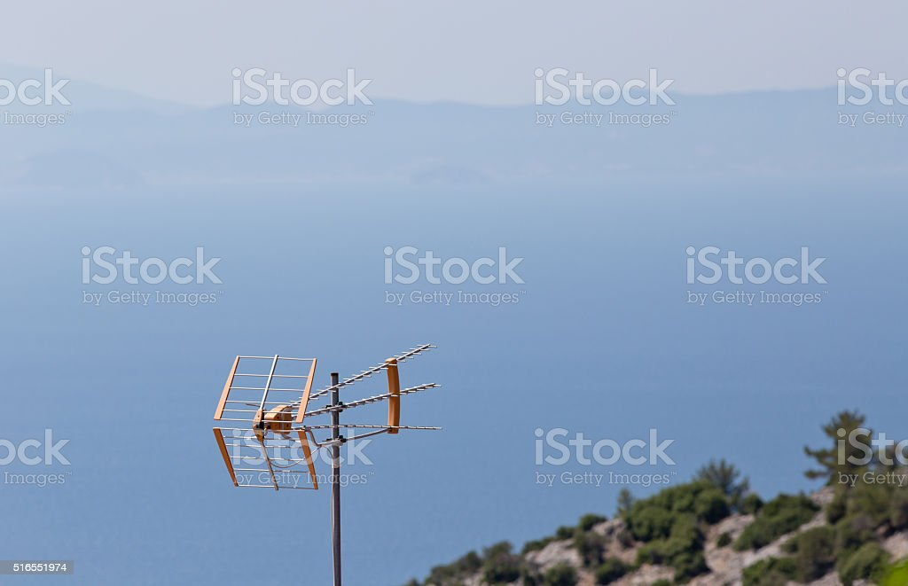 Tv antenna with mountains and seaside in background stock photo