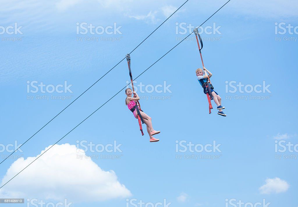 Tw kids playing on a zip line view from below stock photo