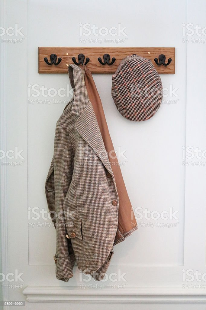 Tweed jacket and flat cap hanging on blue wall stock photo