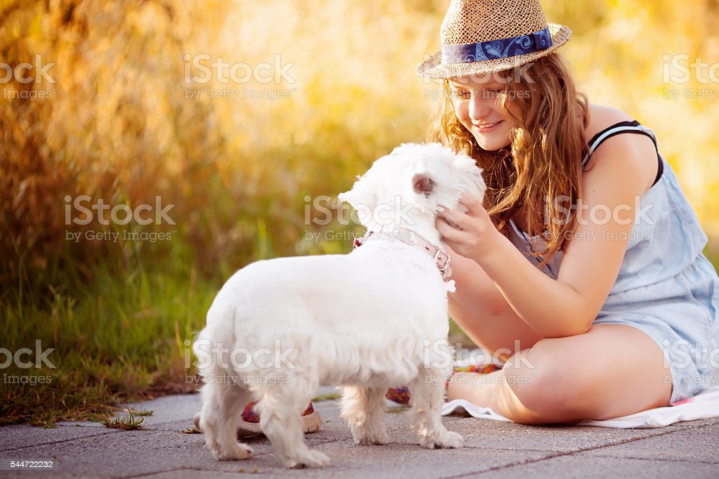 Tween girl in a hat with dog stock photo