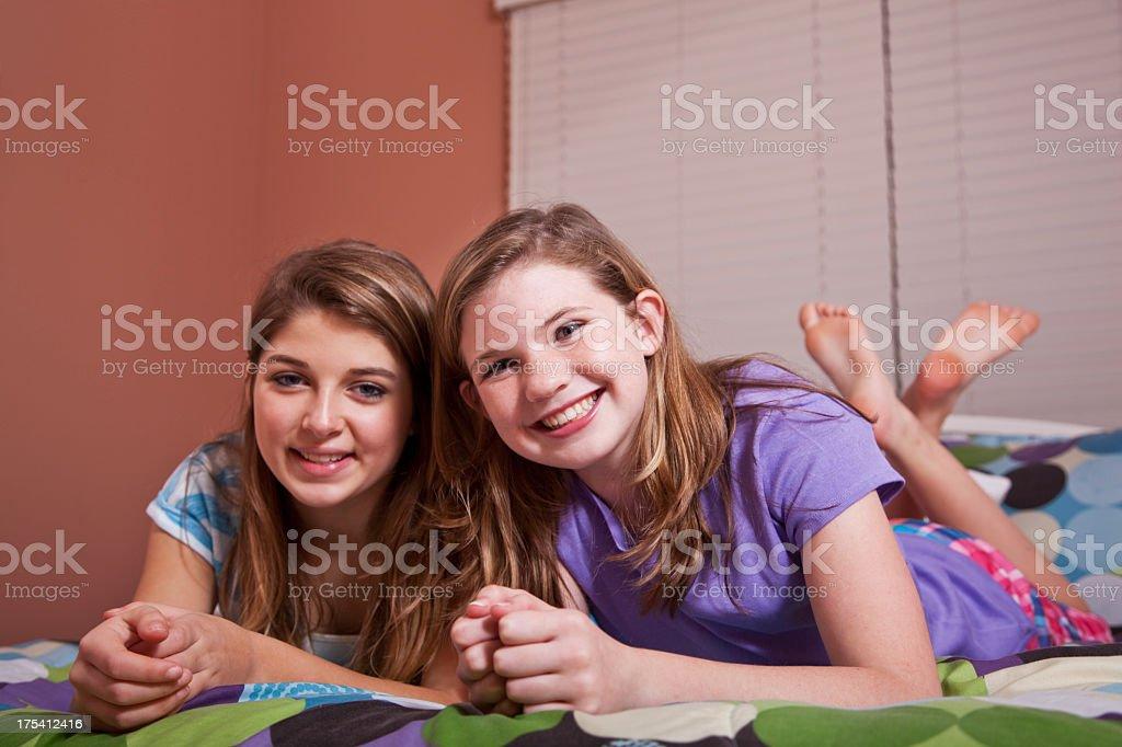 Tween girls on bed stock photo