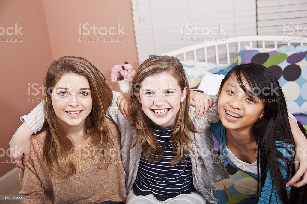 Tween girls sitting on bed stock photo