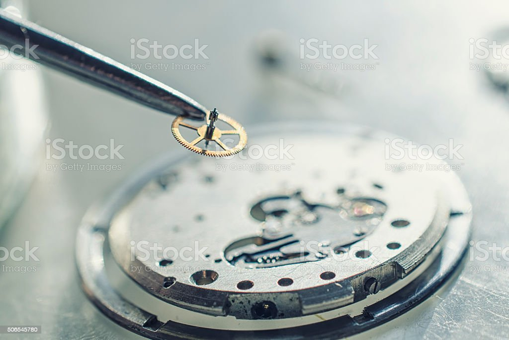 tweezers and disassembled mechanical watches stock photo