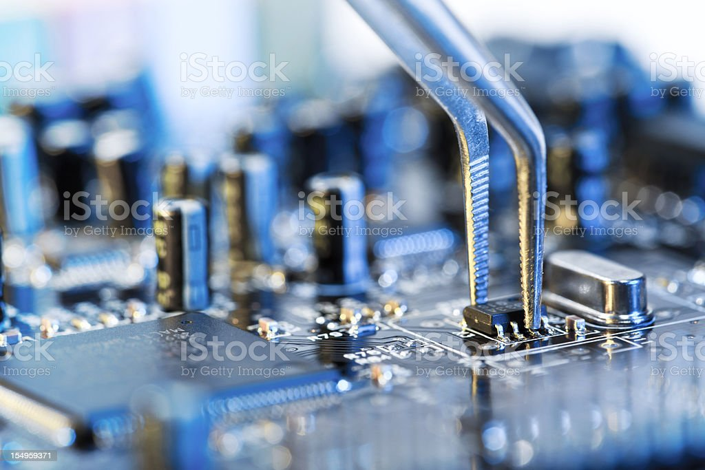 Tweezers grasping microchip on blue computer circuit board royalty-free stock photo