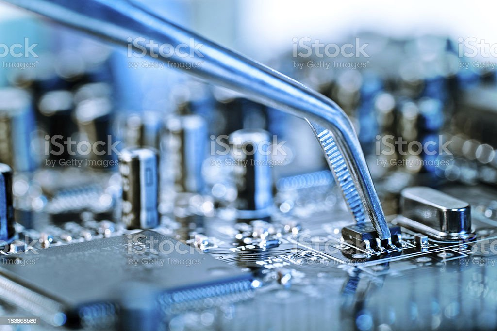 Tweezers grasping microchip on blue computer circuit board stock photo