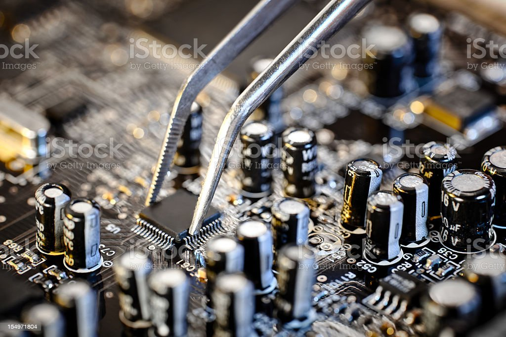 Tweezers grasping microchip on brown computer circuit board royalty-free stock photo
