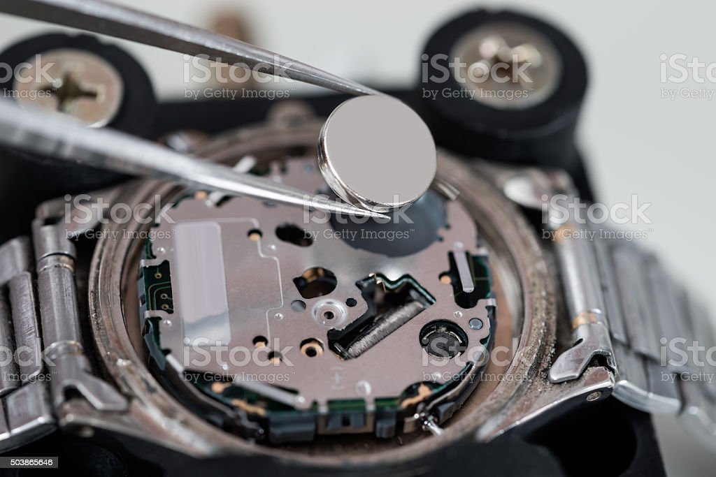 Tweezers With Battery And Wrist Watch stock photo
