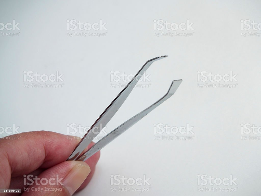 Tweezers with hand on white blackground stock photo