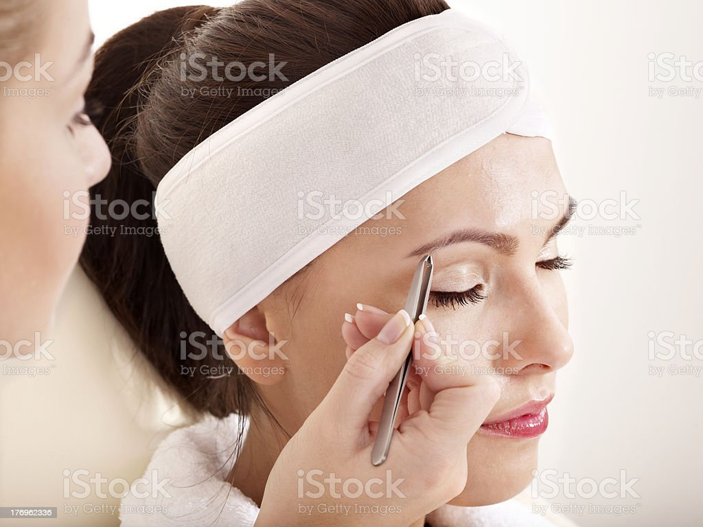 Tweezing eyebrow by beautician. stock photo