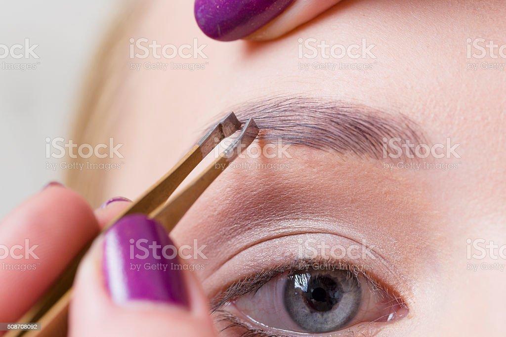 Tweezing Eyebrows stock photo