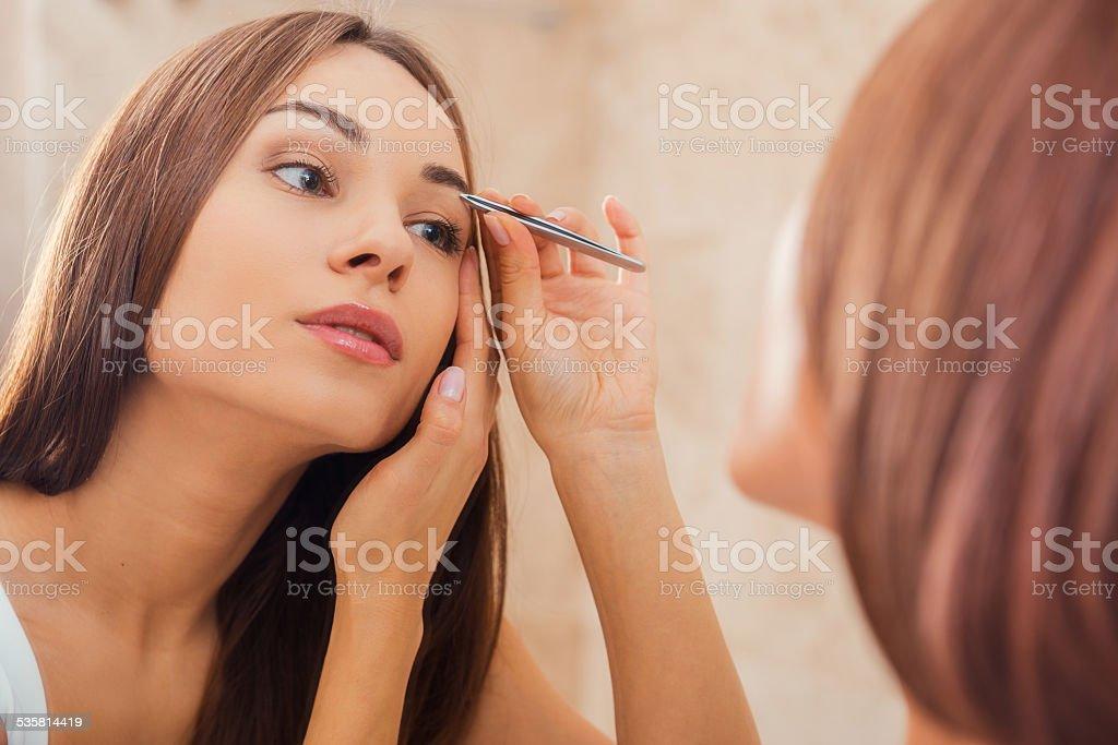Tweezing eyebrows. stock photo