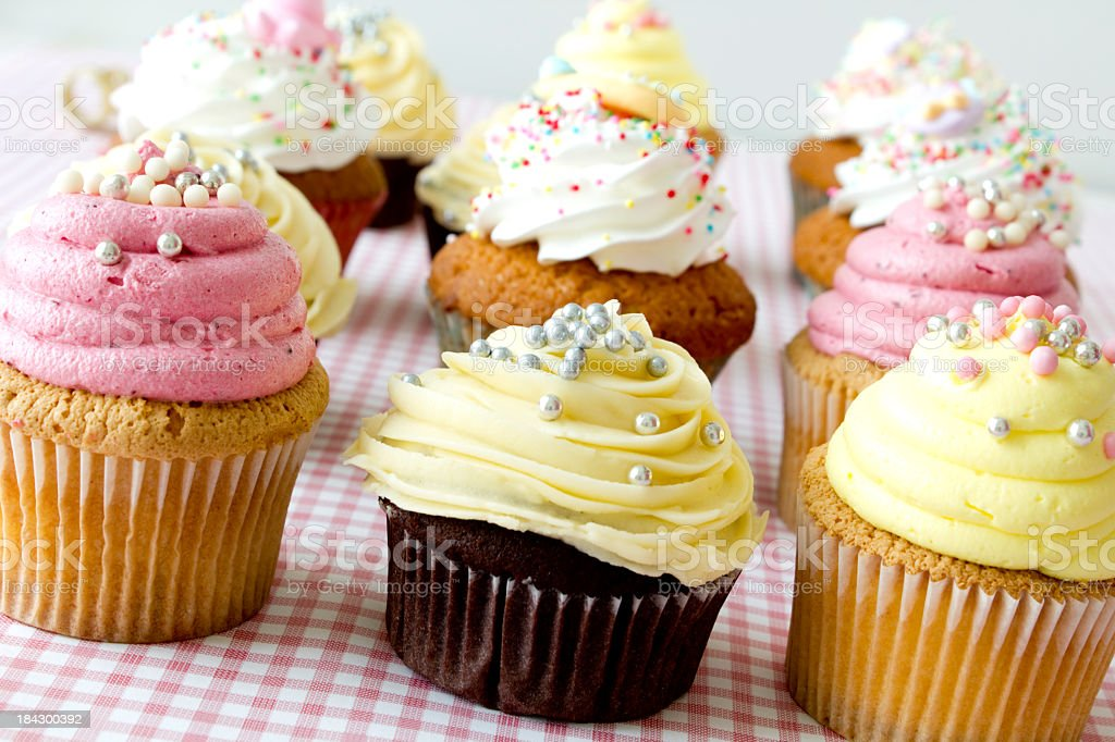 Twelve cupcakes with frosting and sprinkles on checker cloth royalty-free stock photo
