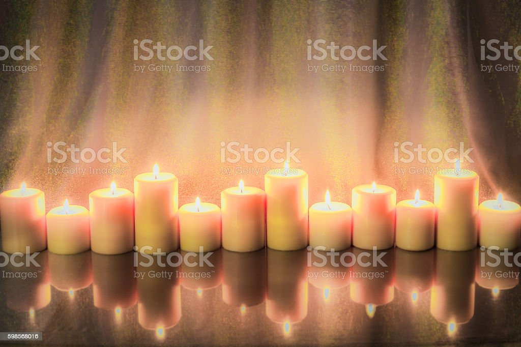 Twelve lit white Candles in a row on mirror (P) stock photo