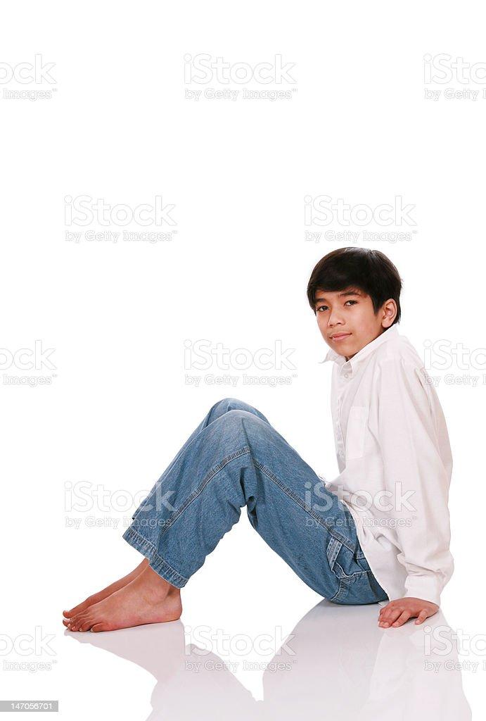 Twelve year old boy sitting on floor stock photo