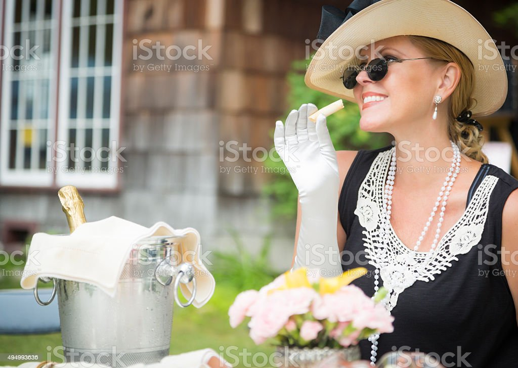 Twenties Dressed Woman Eating and Drinking Champagne Outdoors stock photo