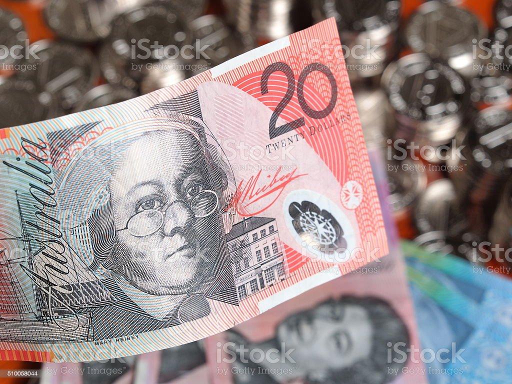 Twenty Australian Dollar note on front of glittering coins stock photo
