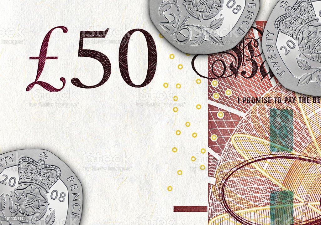 Twenty pence coins on a bill of £ 50 royalty-free stock photo