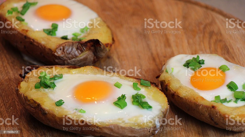 Twice baked potato on a wood board stock photo