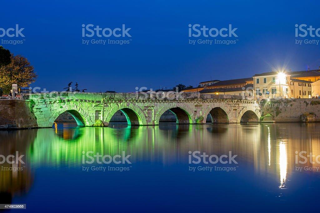 Twilight on cityscape. Rimini, historical Tiberius bridge. stock photo