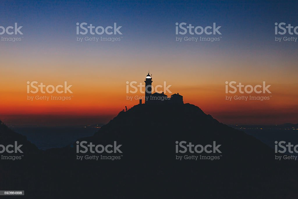 Twilight over hill and lighthouse on top stock photo