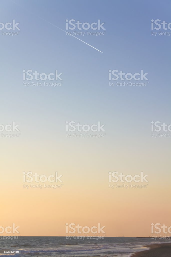 twilight sky gradient with jet trails stock photo