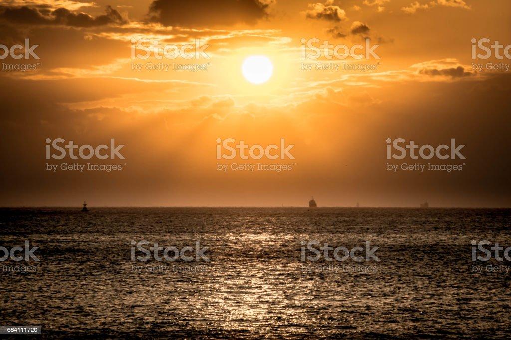 Twilight view is sunset at Kobe bay, cargo ship at the horizontal skyline, has Akashi Kaikyo bridge to Iwaya on Awaji Island, Japan. stock photo
