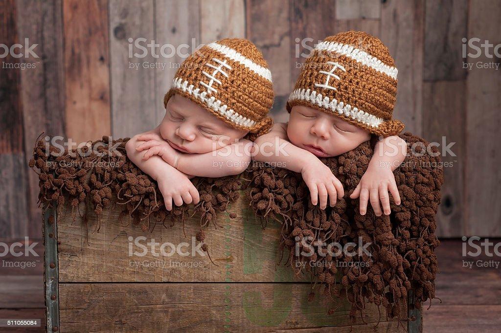 Twin Baby Boys Wearing Football Shaped Hats stock photo