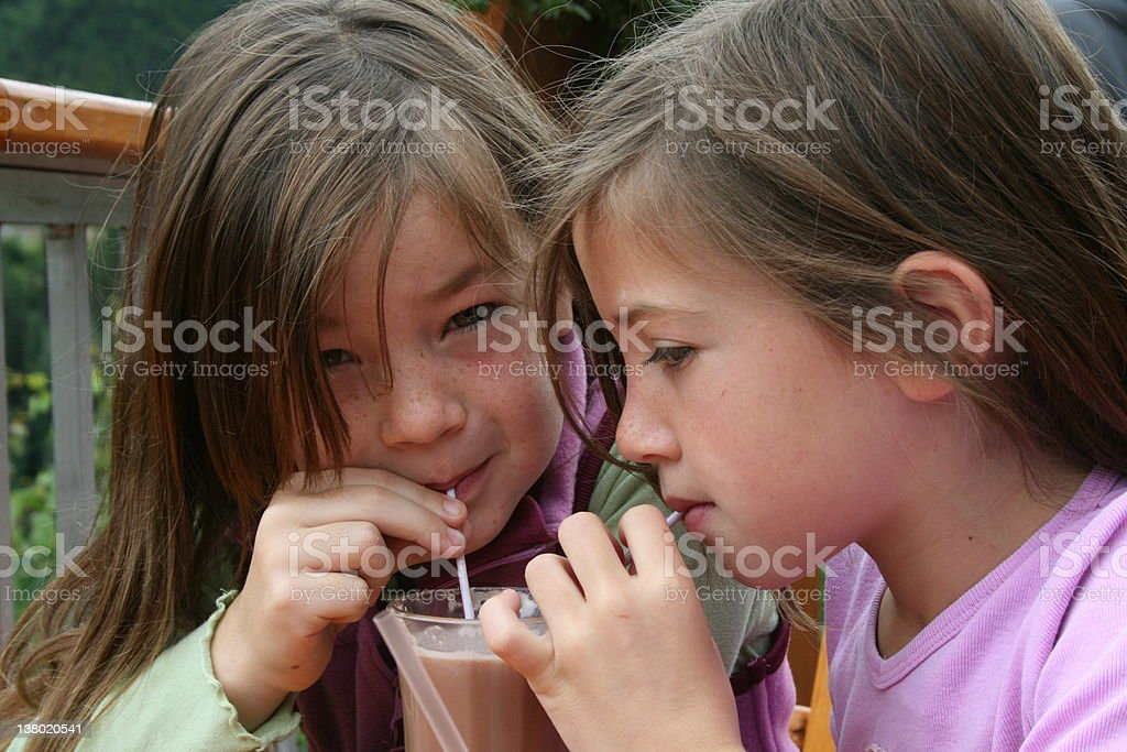 Twin brunette girls drinking cocoa through straws royalty-free stock photo