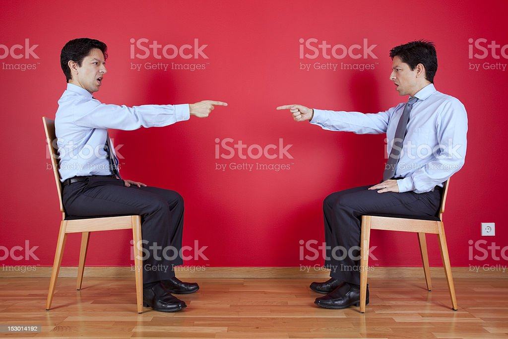 Twin businessmen pointing at each other looking upset royalty-free stock photo