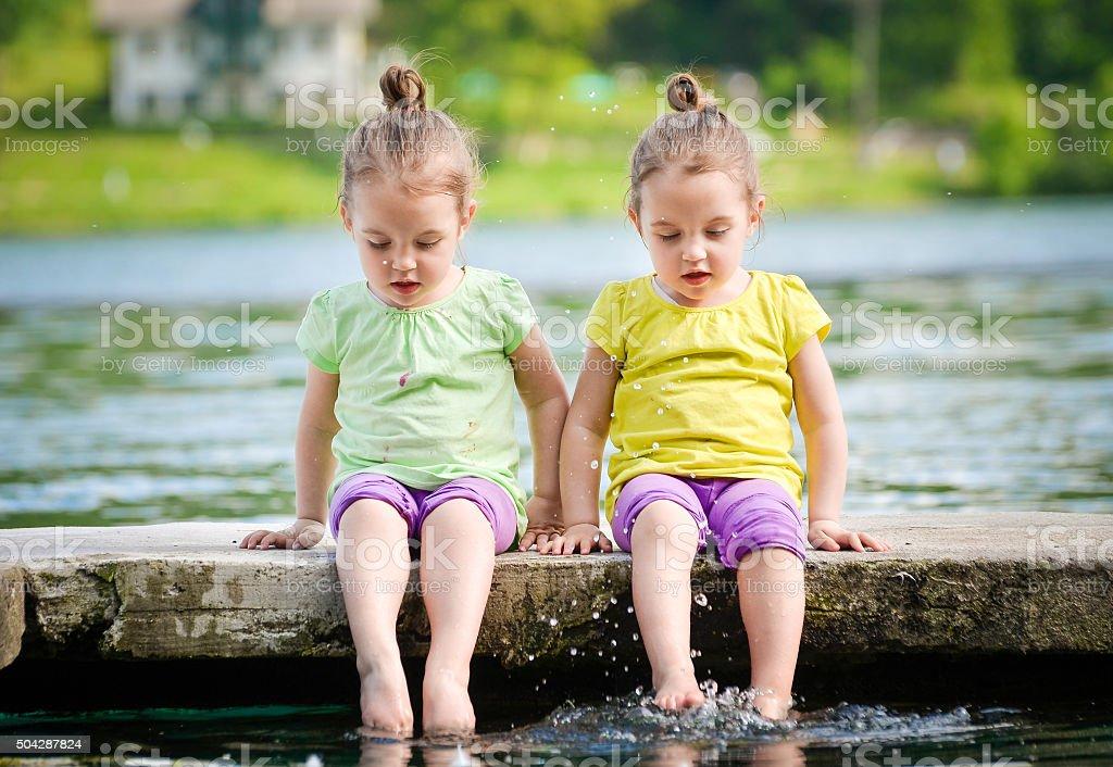 Twin girls exercising on a lake shore stock photo
