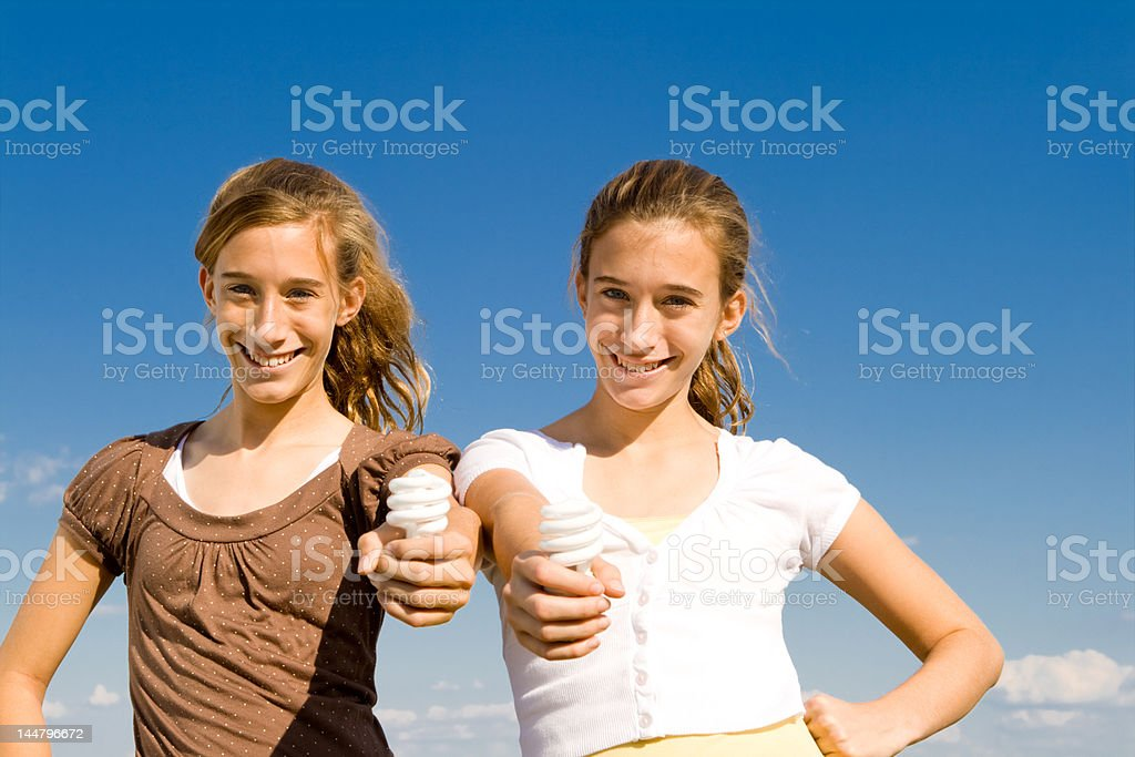 Twin Girls Holding Compact Fluorescent Light Bulbs, Blue Sky royalty-free stock photo