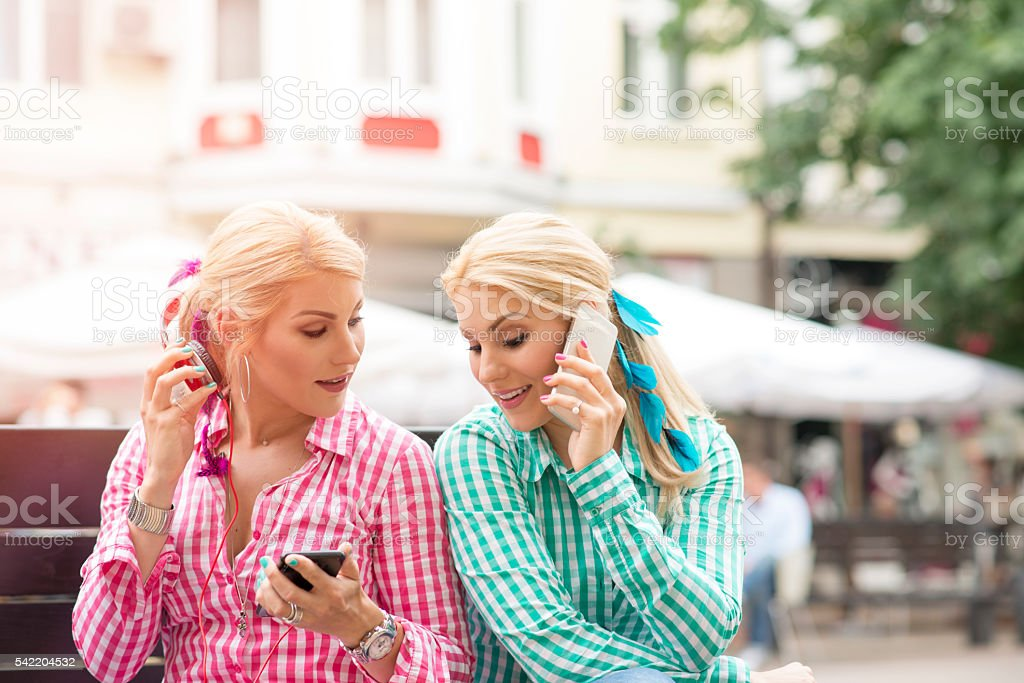 Twin girls in red and green with phones stock photo