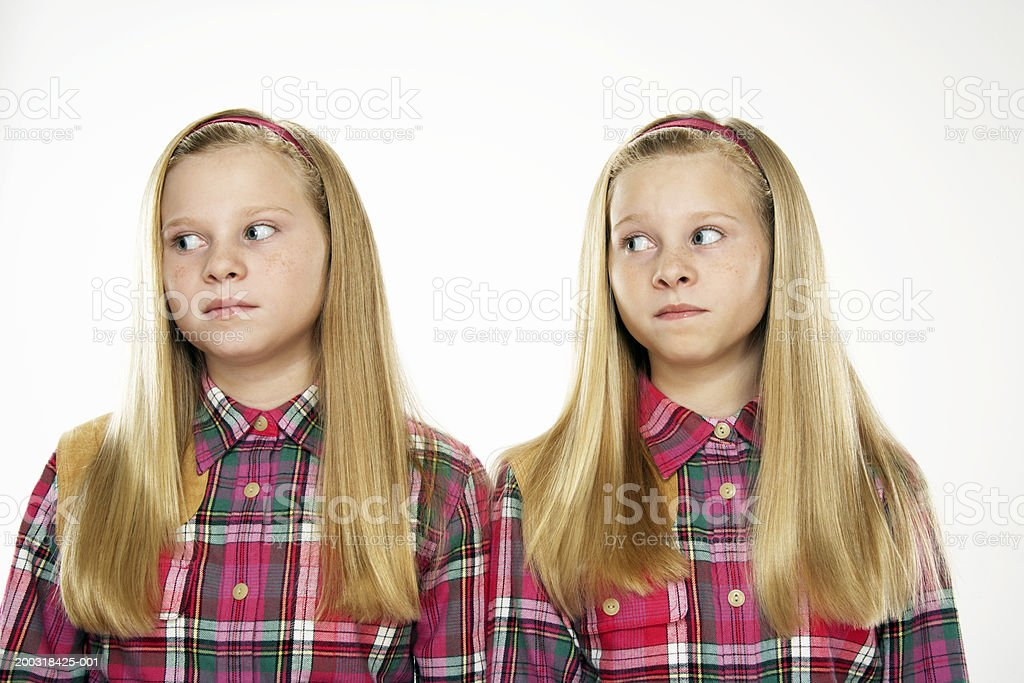Twin girls (10-12) looking sideways, close-up royalty-free stock photo