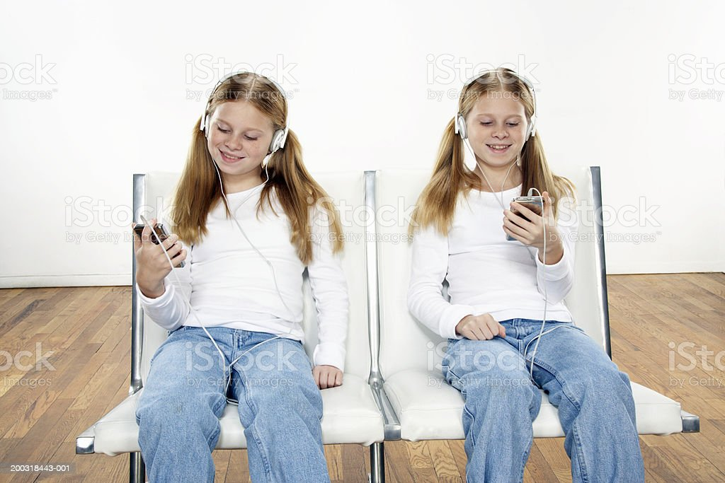Twin girls (10-12) sitting side by side, listening to MP3 players, smiling stock photo