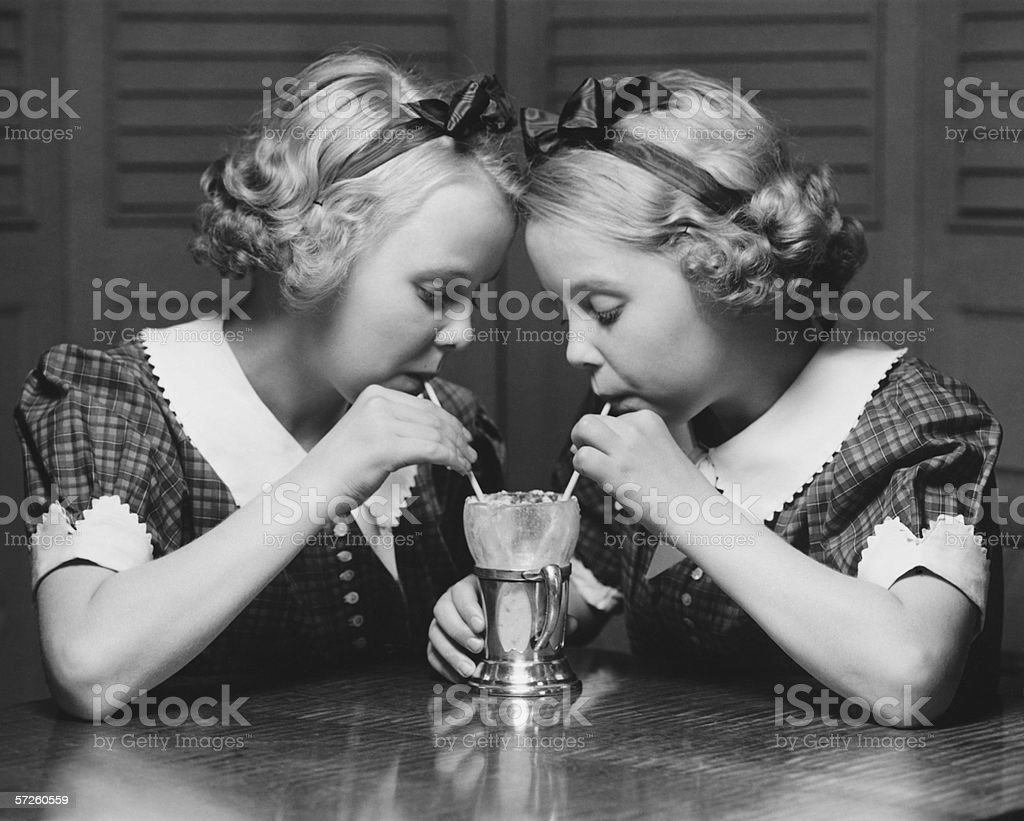 Twin sisters (12-13) drinking through straws from same glass, (B&W) royalty-free stock photo