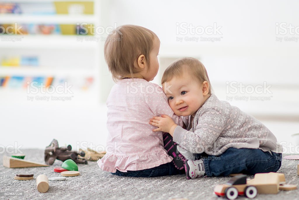 Twin sisters hugging in preschool. stock photo