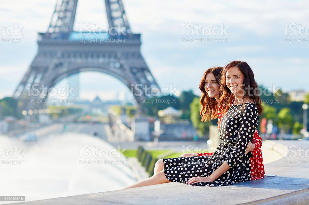 Twin sisters in front of the Eiffel tower in Paris stock photo