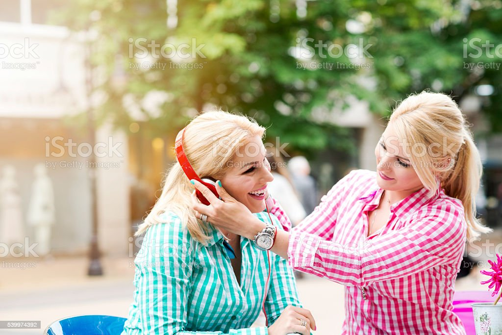 Twin sisters listening music stock photo