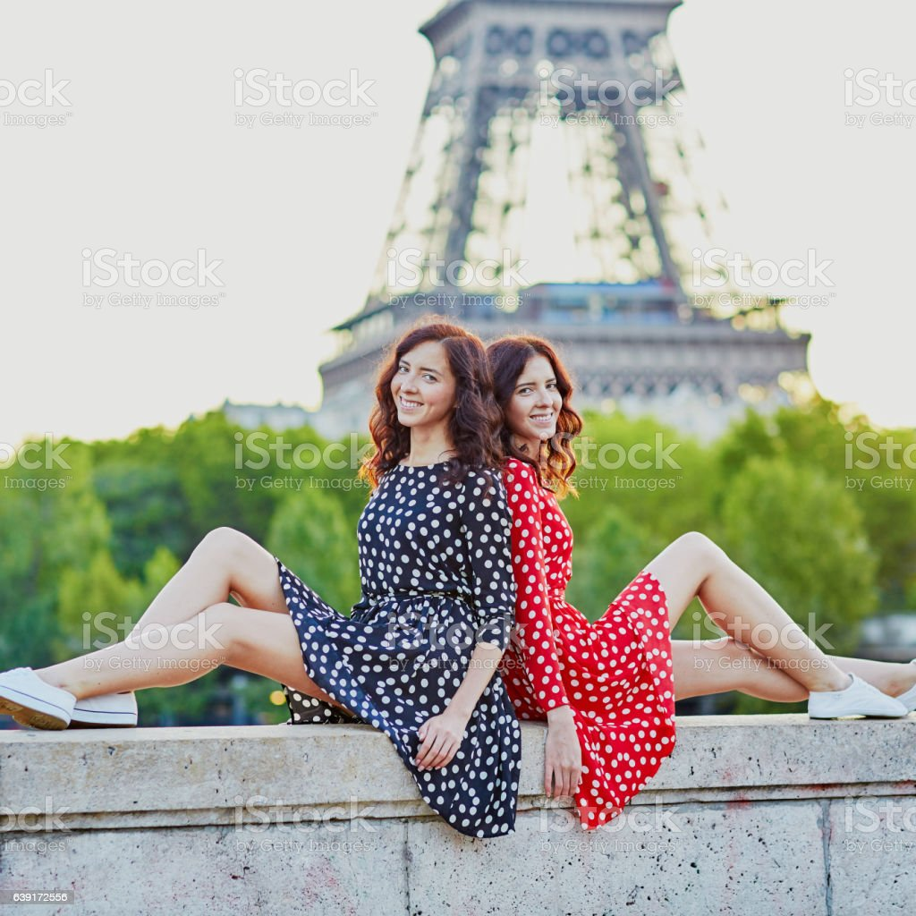 Twin sisters near the Eiffel tower in Paris, France stock photo