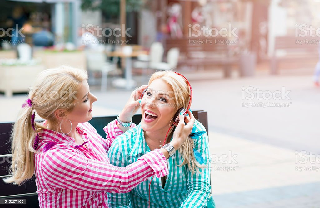 Twin sisters sharing and listening to music stock photo