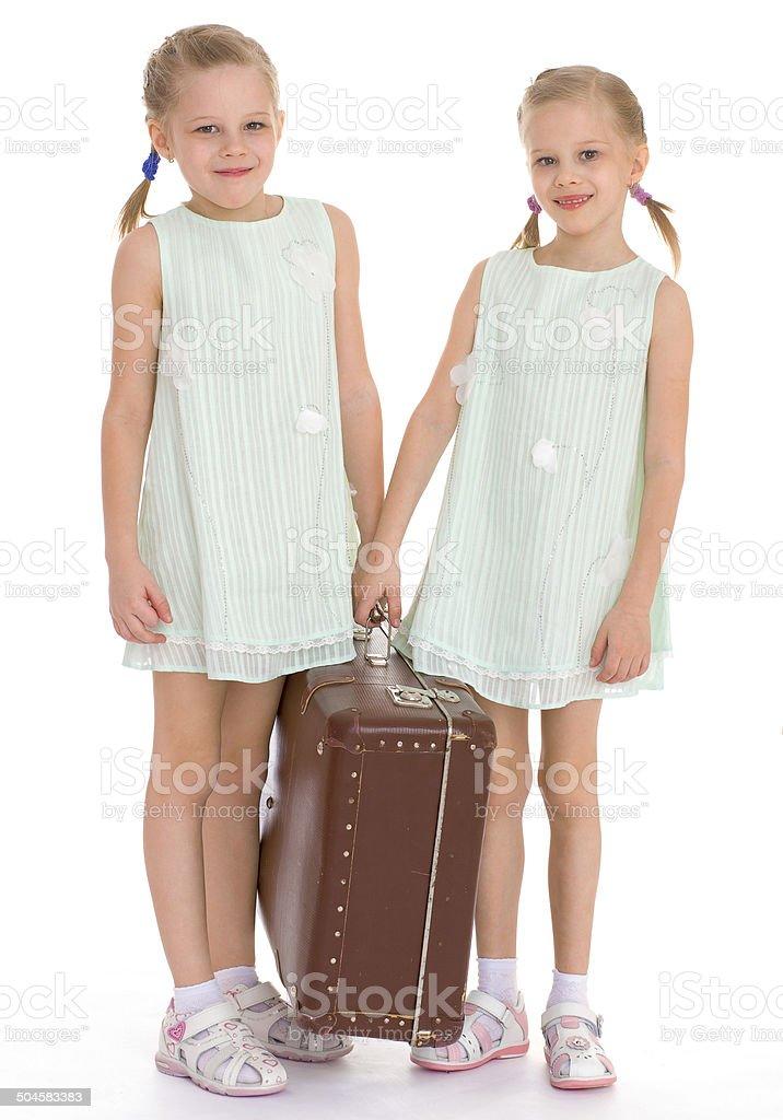 twin sisters avec un gros vieille valise. photo libre de droits
