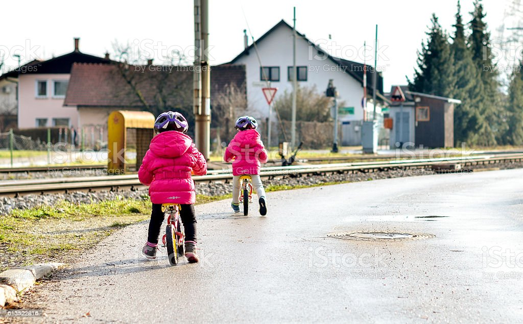 Twins children riding balance bikes on the road with helmet. stock photo