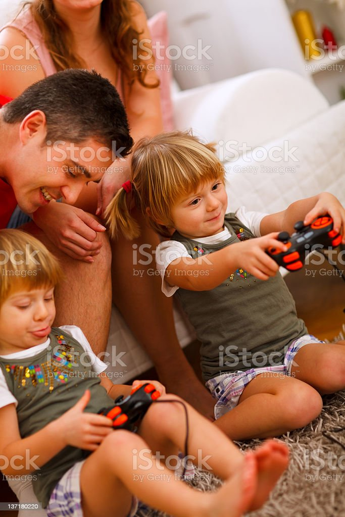 Twins daughters playing on console at home royalty-free stock photo