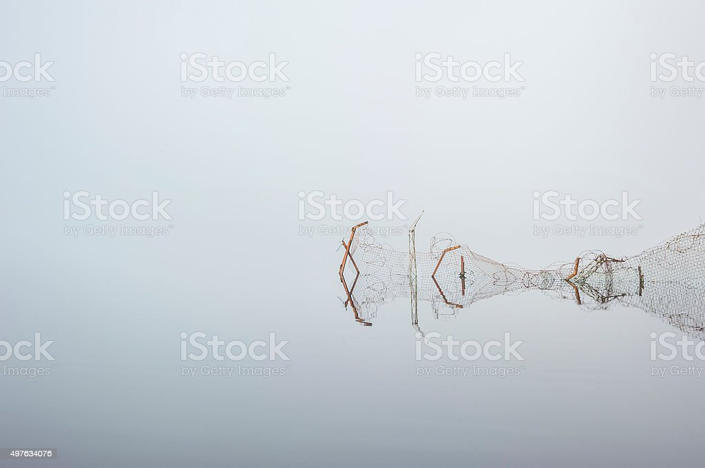 twisted fence in mirror calm lake stock photo