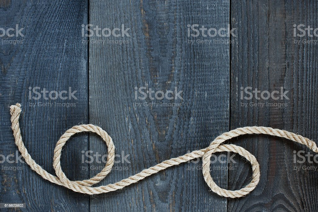 Twisted rope on the old wooden background stock photo