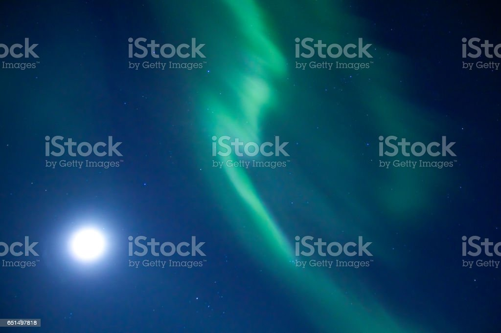 Twisting Aurora borealis with a white moon and shining stars stock photo
